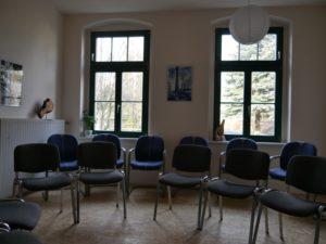 Seminarraum mit Stühlen vor zwei Fenstern