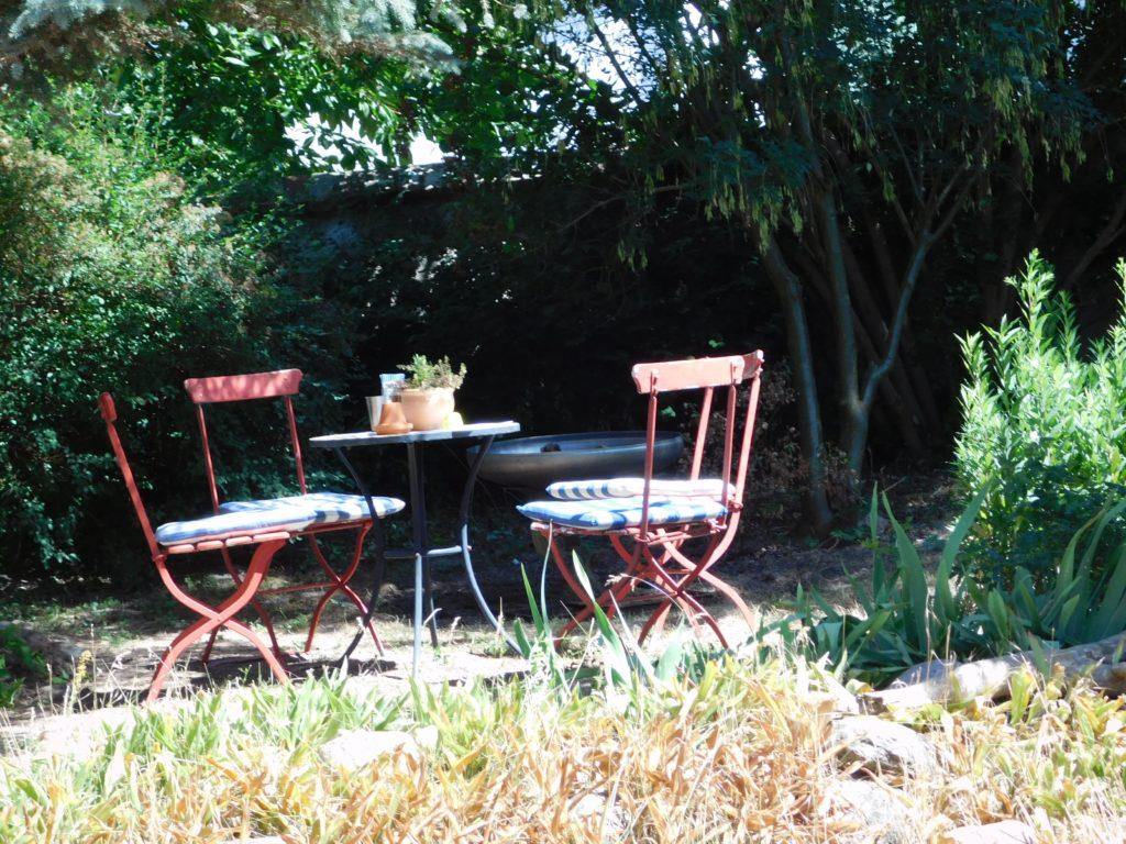 Tisch mit roten Stühlen im Garten